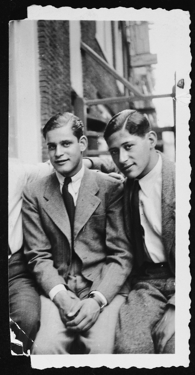 Two teenagers visit together on a porch of an apartment.  Pictured on the right is Erich Zielenziger, a Jewish immigrant from Berlin, and on the left is his friend, Claus Forstenzer.