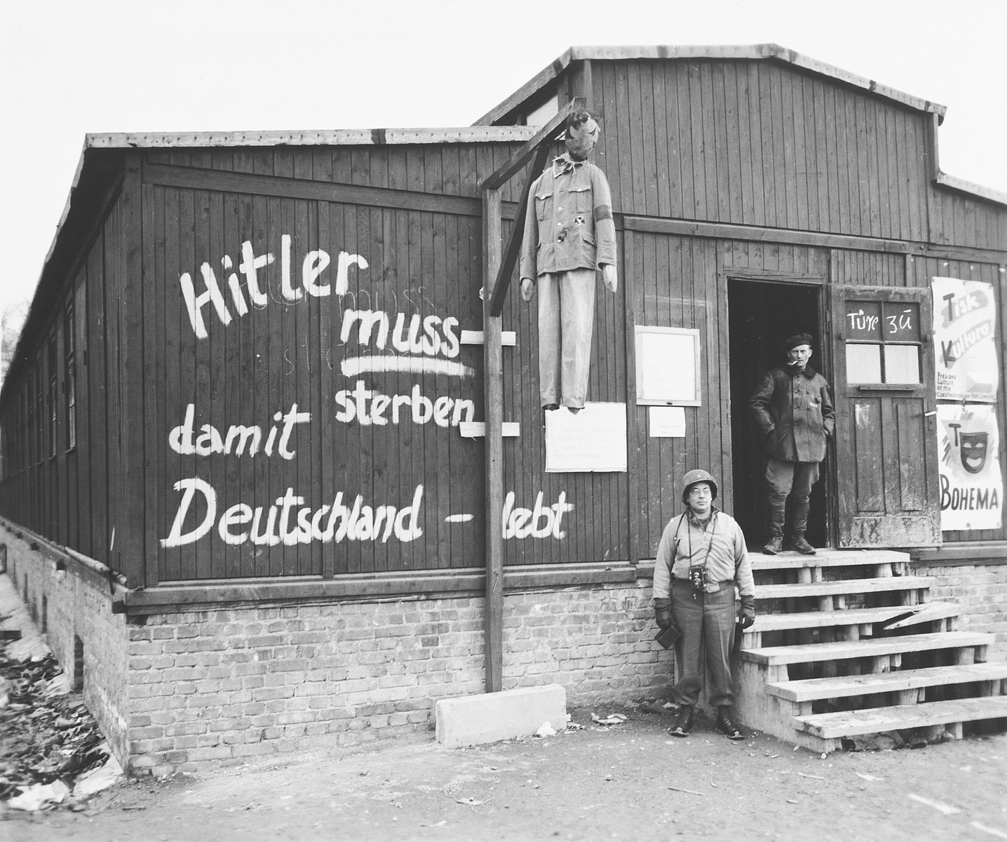 "An American soldier poses next to an effigy of Hitler hanging in front of a barracks in the Buchenwald concentration camp.  Grafitti on the side of a barracks reads ""Hitler must die for Germany to live""."
