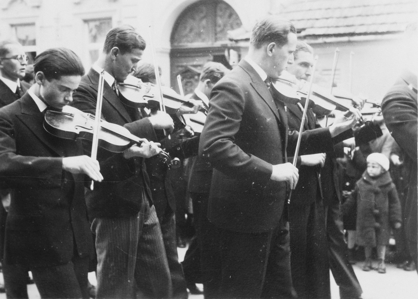 Graduates of a Gymnasium in Budapest parade to the commencement excercises playing the violin.  Among those pictured is Denes Simonyi (left), one of three Jewish students.