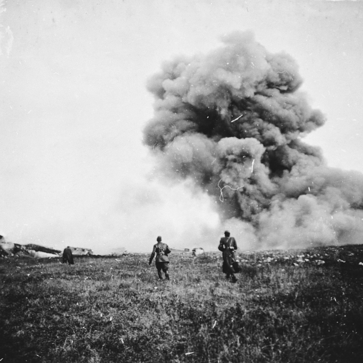 """Members of a Hungarian forced labor battalion run from an explosion [in Oradea] where they are accompanying the Hungarian army's advance into Transylvania.  The original caption reads, """"After the explosion, a cloud of smoke."""""""