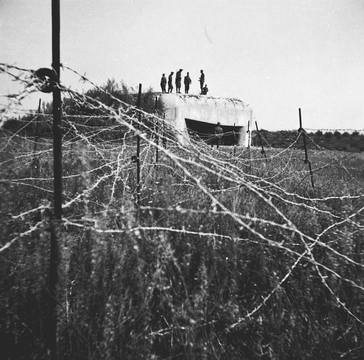 Members of a Hungarian forced labor battalion stand on top of a bunker behind a barbed wire fence in Oradea, where they are accompanying the Hungarian army's advance into Transylvania.