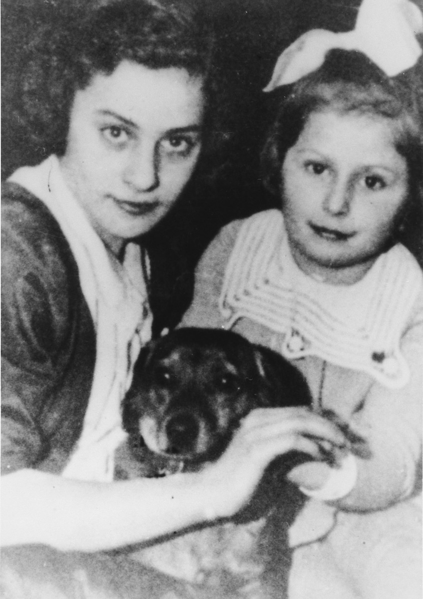 """Two Polish Jewish children pose with their dog.  Pictured are Estusia Wajcblum and her younger cousin Jeannette (""""Janka"""") Jaglom (later Tokatly).  Janka was the daughter of Moisej Jaglom."""