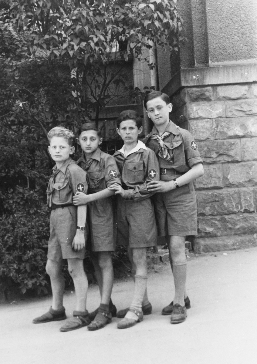 Four young members of Hashomer Hatzair pose standing in a row in the Stuttgart displaced persons' camp.  Lova Warszawczyk is pictured on the far right.