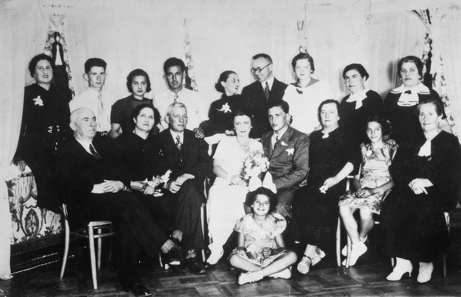 Portrait of a Polish Jewish family at a wedding.  Pictured are Hanka Wajcblum (seated in front), Estusia Wajcblum (seated second from right), Rebeka (Jaglom) Wajcblum (back row, left), and Sabina Wacjblum (back row, third from left).