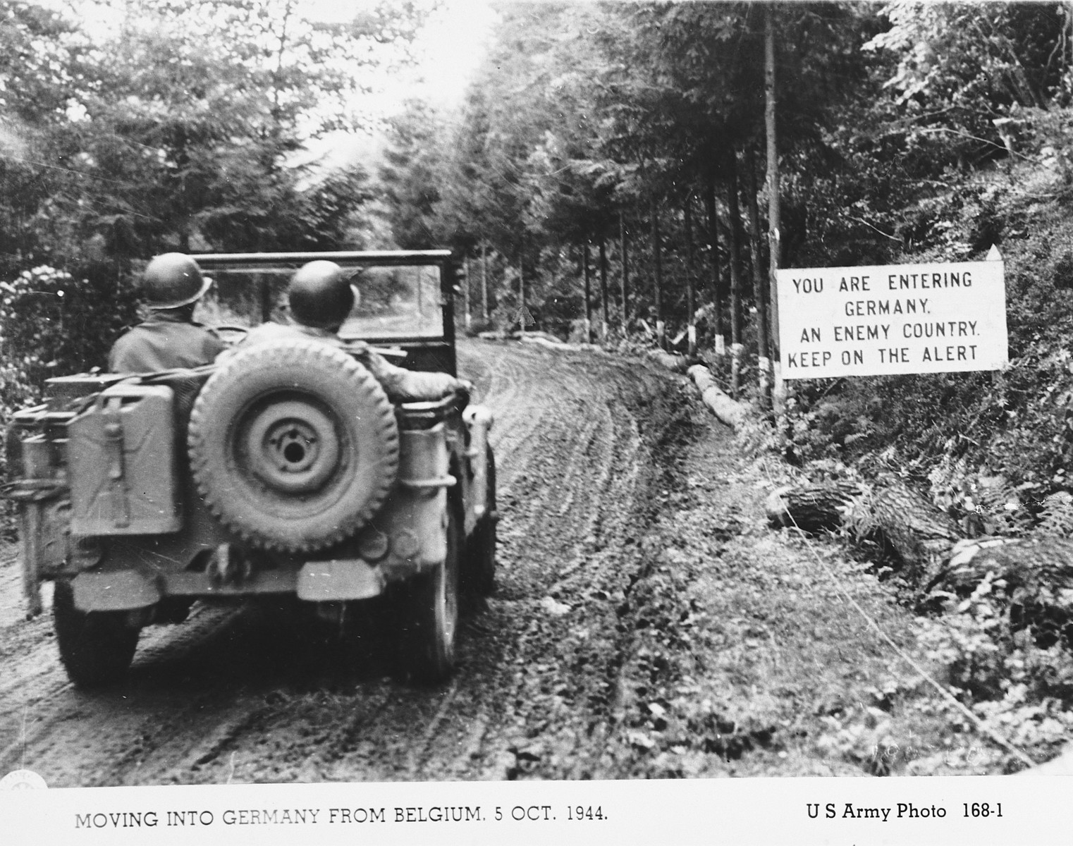 "Two American soldiers in a jeep drive into Germany from Belgium.  To their right is a sign in English that says, ""You are entering Germany, an enemy country.  Keep on the alert."""