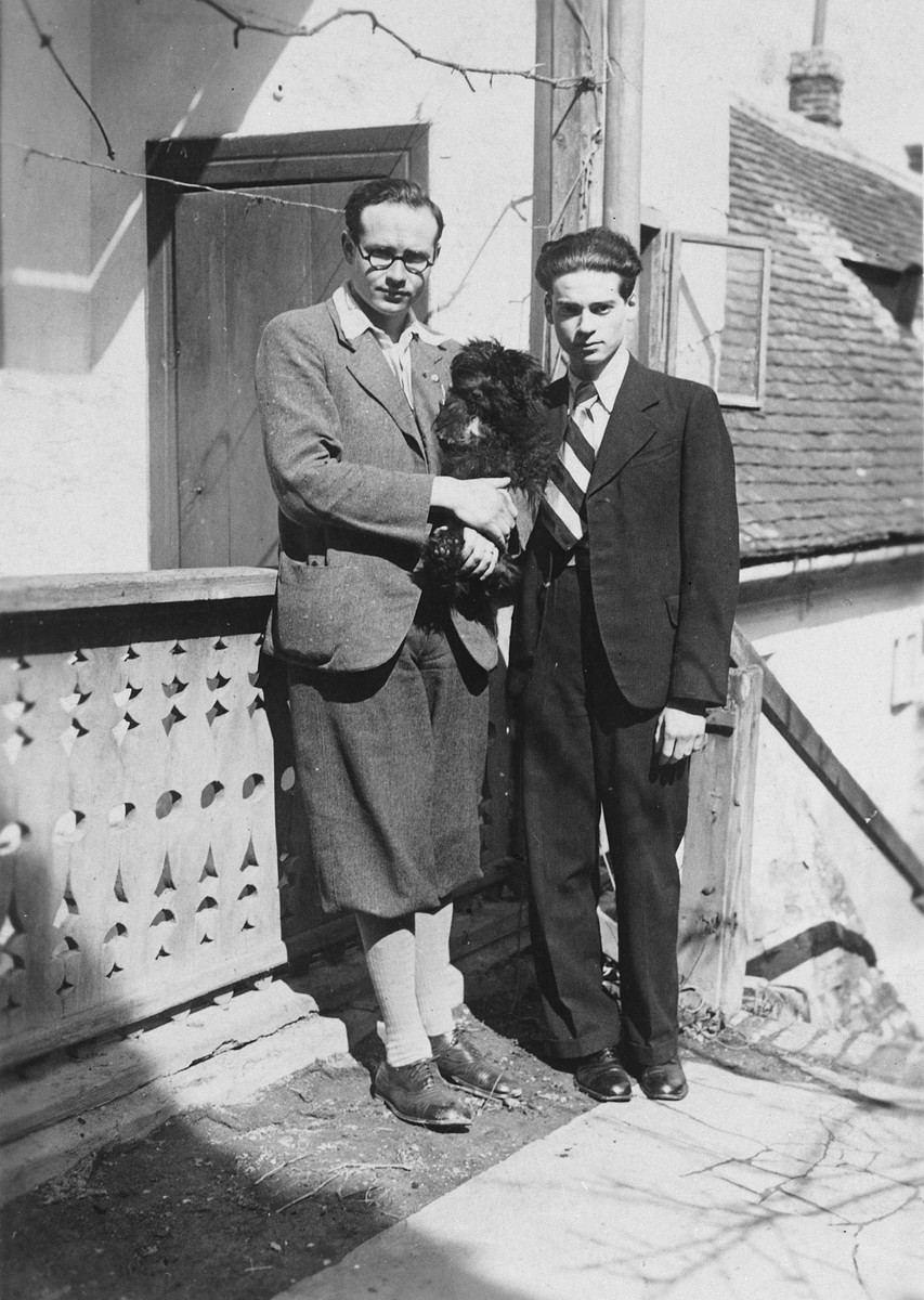 "Two Hungarian Jewish brothers pose outside their home holding their pet dog, ""Puli.""  Pictured are Bandi and Denes Simonyi."