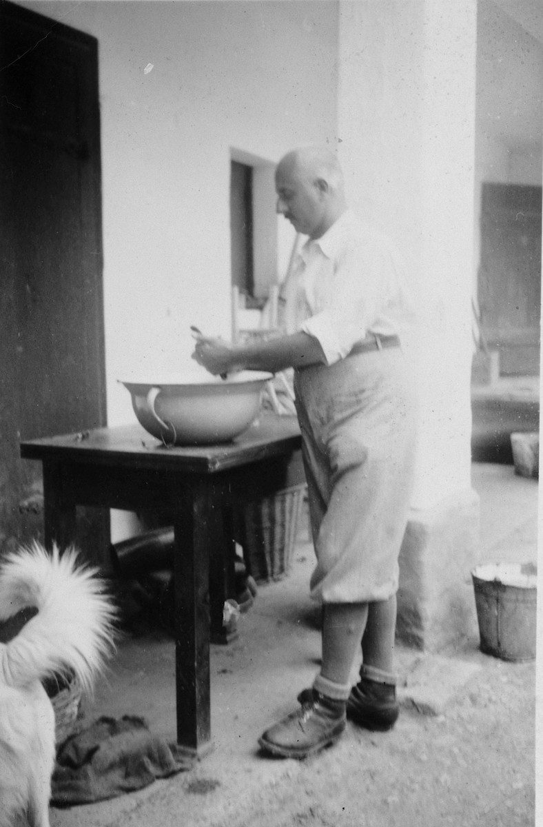 A Hungarian Jewish man prepares food in a large bowl on a wooden table.  Pictured is Lajos Beke.  He later died in the Holocaust.