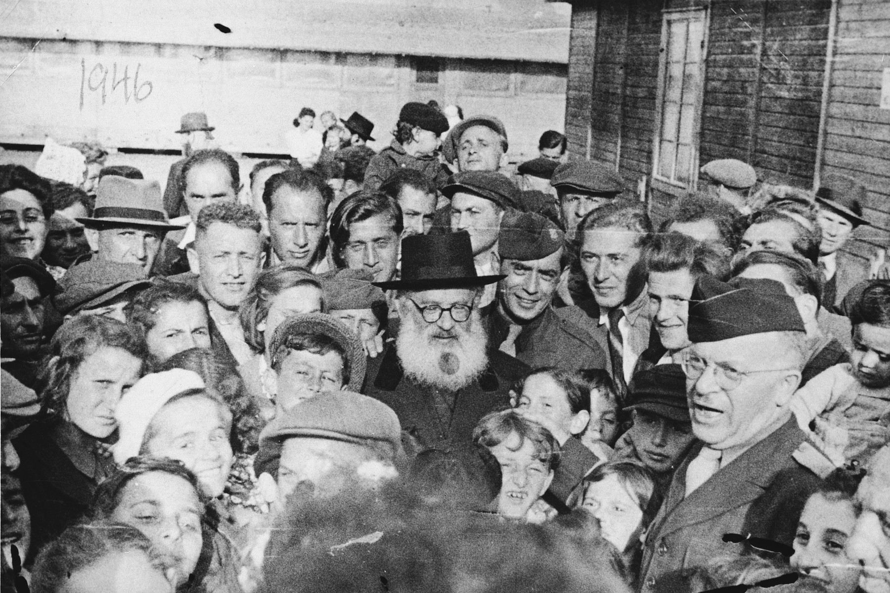 Rabbi Isaac Herzog pays an official visit to the Neu Freimann displaced person's camp.  Among the children crowded around him is Lova Warszawczyk.