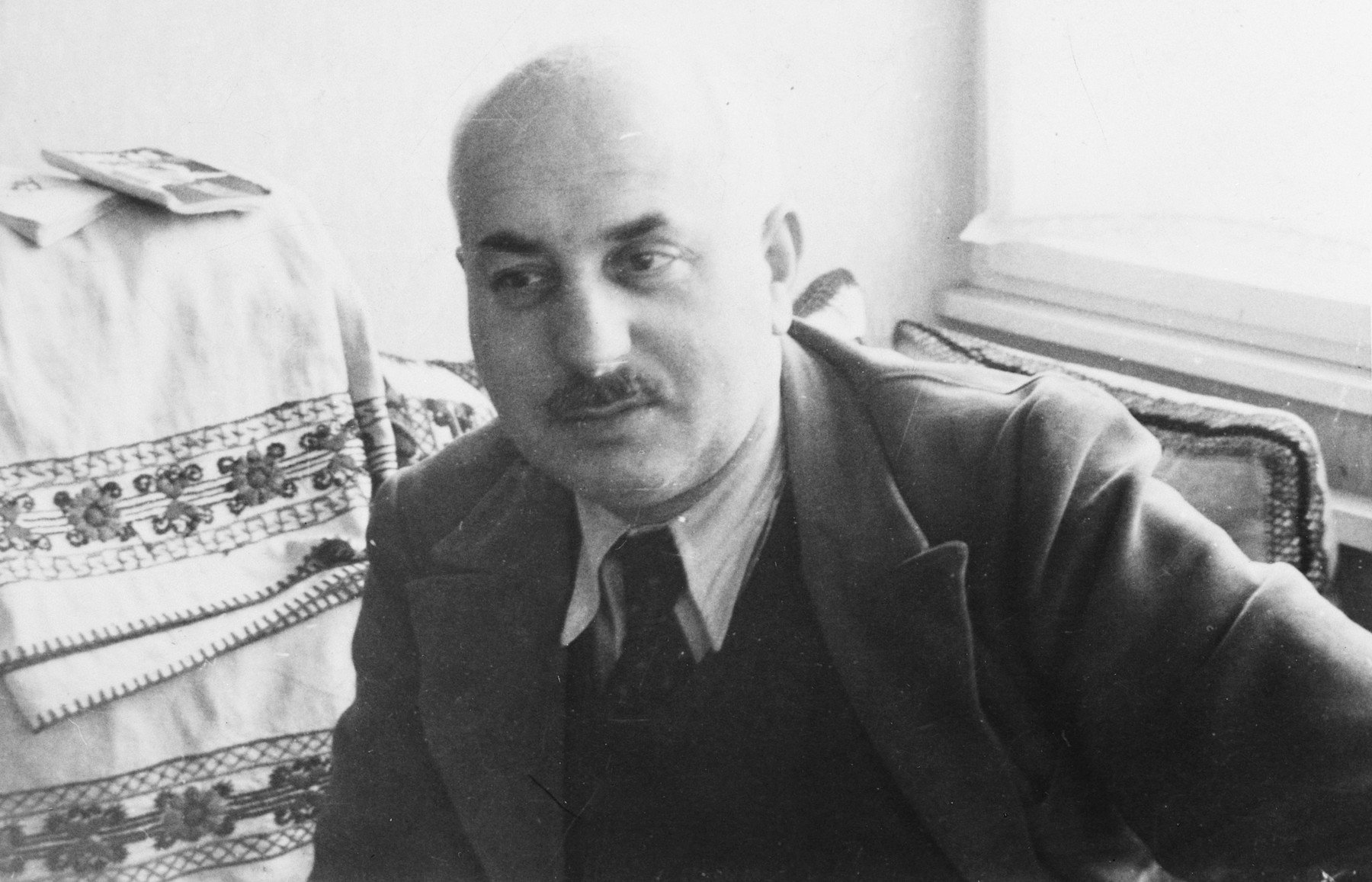 Close-up of a Hungarian Jewish textile manufacturer sitting in his home next to an embroidered cloth.  Pictured is Lajos Beke.  He later died in the Holocaust.