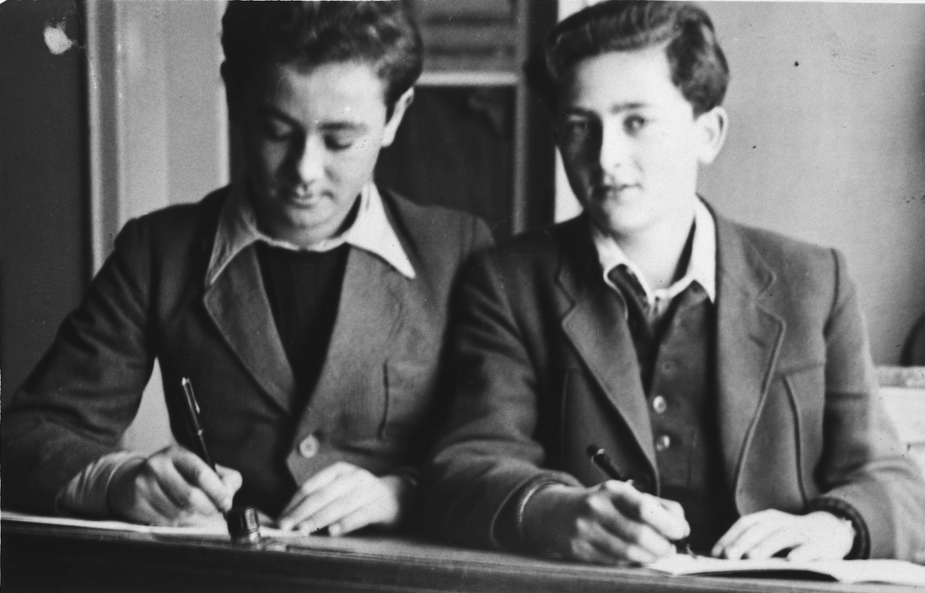 Two school boys work at their desk in the Stuttgart displaced persons camp.  Lova Warszawczyk is on the left; Jack Krampf is on the right.
