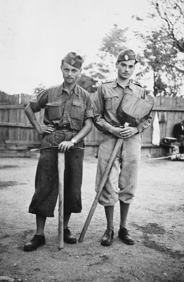 Two members of a Hungarian forced labor battalion pose holding a pick and shovel in Oradea, where they are accompanying the Hungarian army's advance into Transylvania.  Denes Simonyi is pictured on the right.