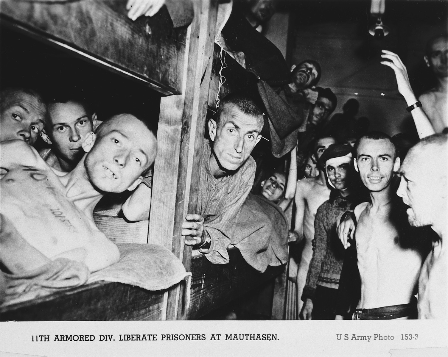 Prisoners liberated from Mauthausen, many crowded into a wooden bunk, celebrate their liberation by the American 11th Armored Division.