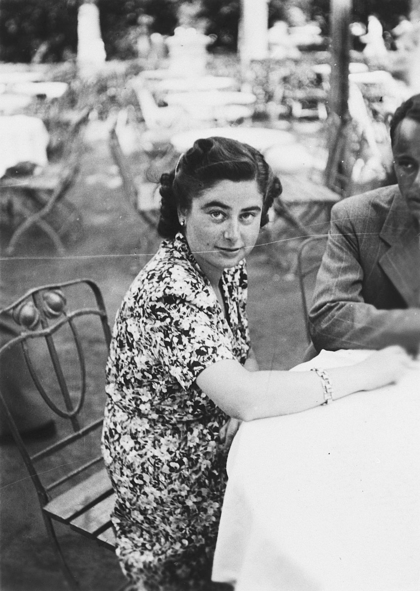 A young Hungarian woman sits at a table in an outdoor cafe in Budapest.  Pictured is Edeke Beke.  She later died in the Holocaust.