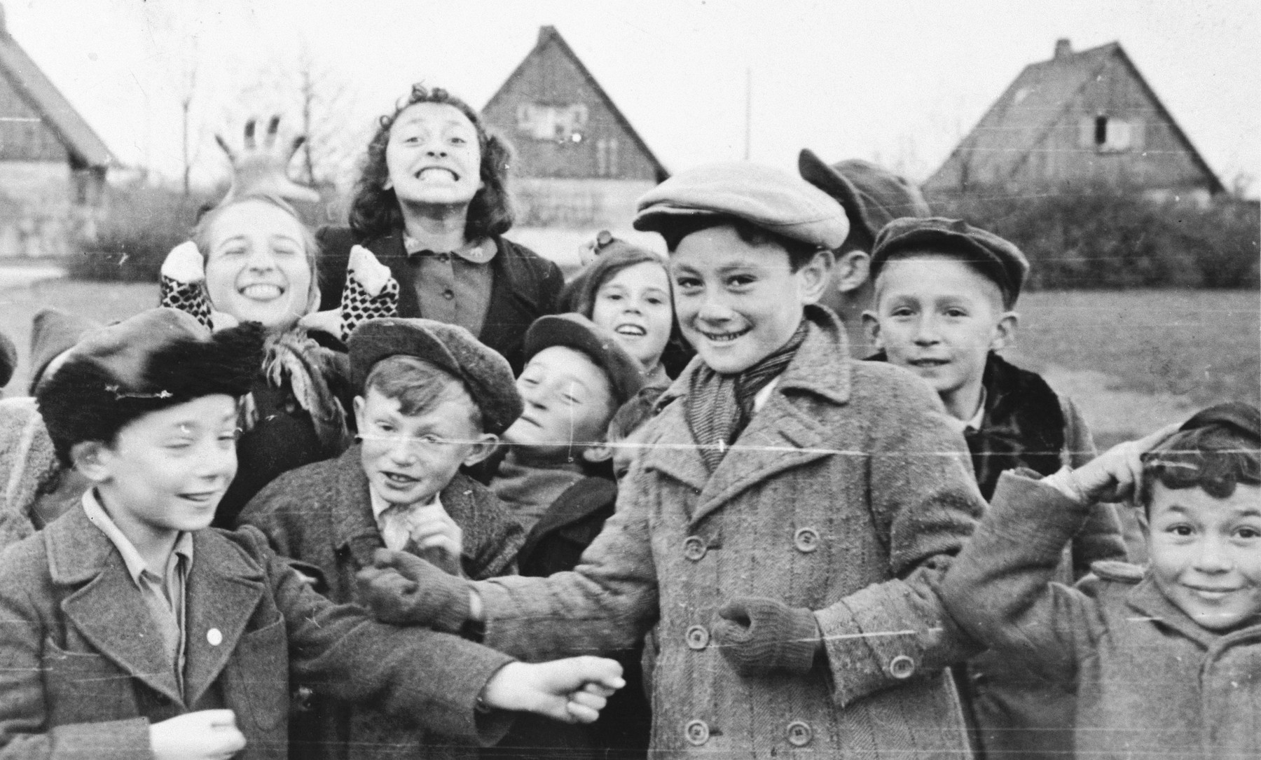 A large group of children stands in humorous poses for a photograph in the Neu Freimann displaced person's camp.  Lova Warszawczyk poses in the foreground.