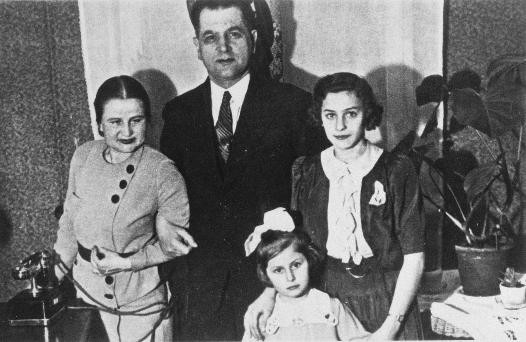 Portrait of a Polish Jewish family.    Pictured are Estusia Wajcblum (far right), her cousin's daughter Yanka (front), Yanka's governess (left), and an unknown man.