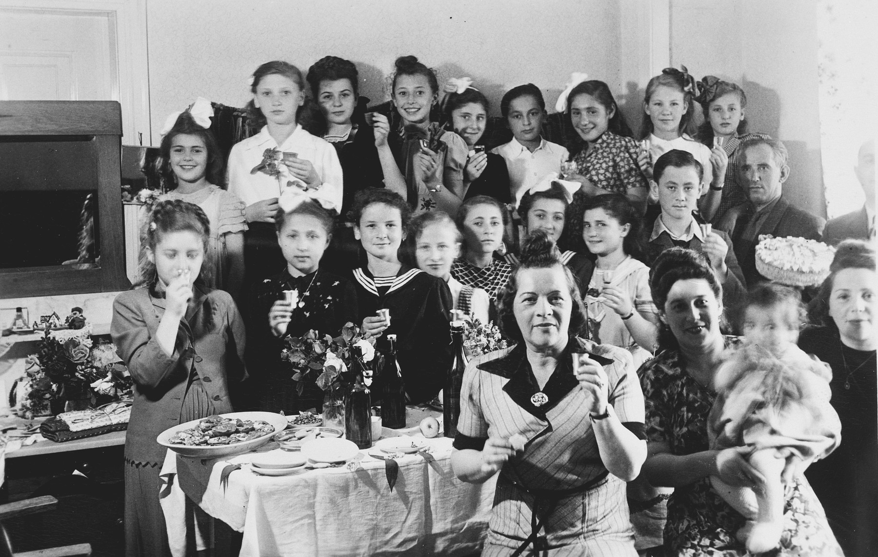 School children hold small silver cups during a celebration in the Stuttgart displaced persons camp.  Among those pictured in the middle row, Irka Hechtkopf, second from the left; Rywka Weinberg, fourth from the left; Hela Huberman, seventh from the left and Lova Warszayczyk (the donor), second from the right.