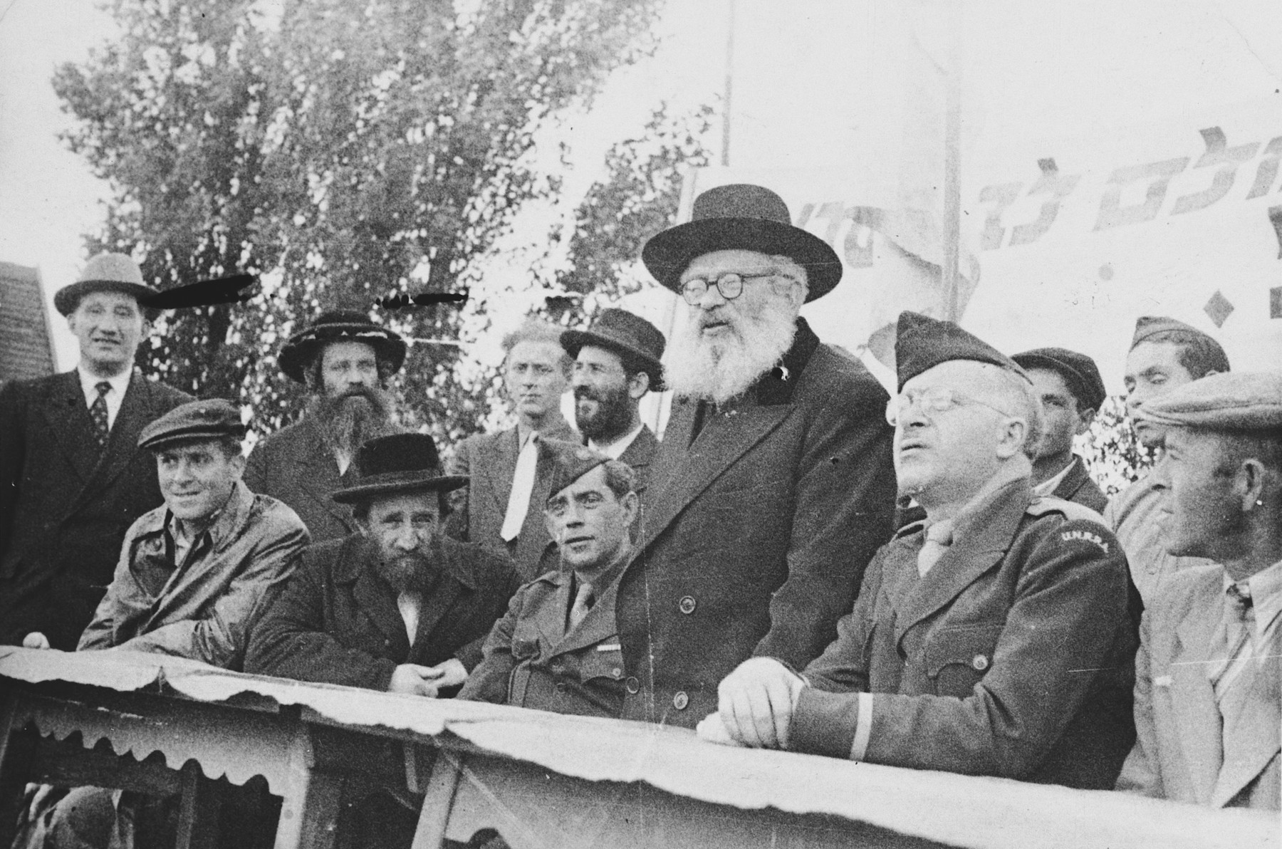 Rabbi Isaac Herzog speaks from a podium during an official visit to the Neu Freimann displaced persons' camp.