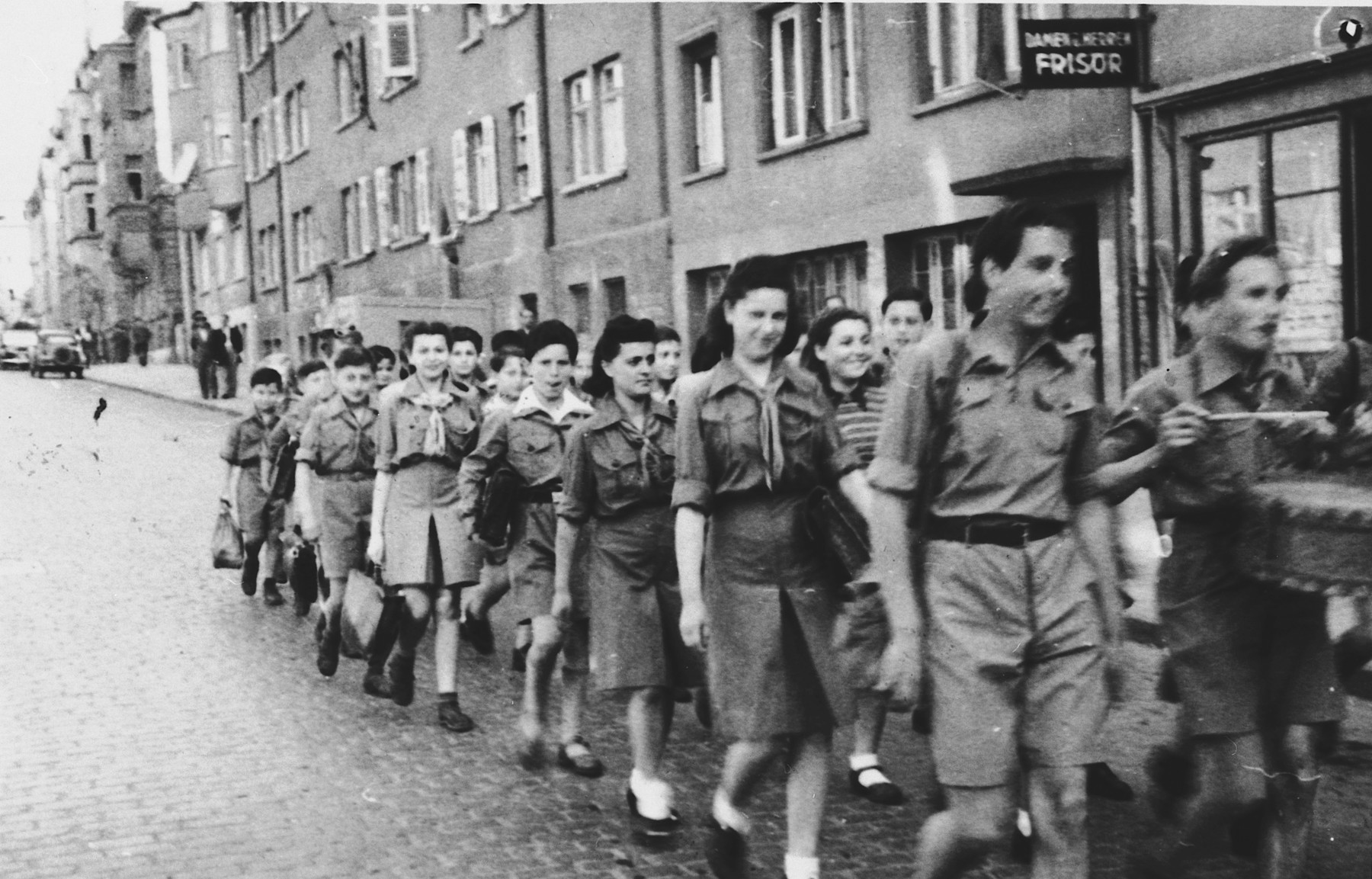 Members of Hashomer Hatzair march in a Zionist demonstration through a commercial street in Stuttgart.  Among those pictured are Basia Kac, second from the left, and Hadasa Eisenberg, fourth from the left.