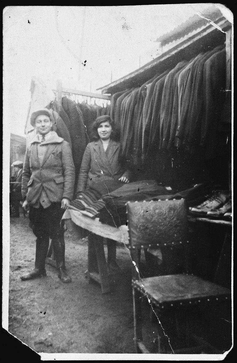 Polish-Jewish immigrants pose in an outdoor market with the suits they have sewn.  Pictured are Sacha and Esther-Rachel Szenker.