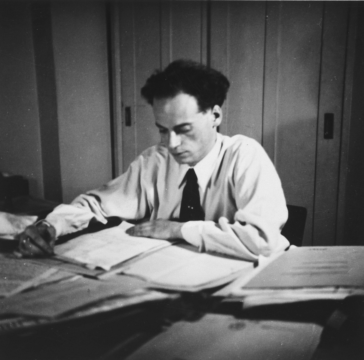 A young Hungarian-Jewish man reads documents at his desk.   Pictured is Denes Simonyi.