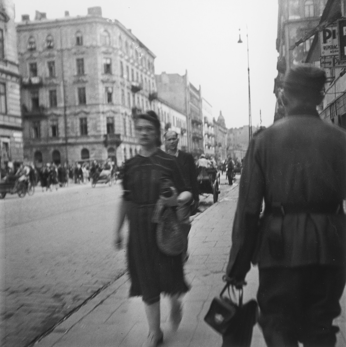 "A Jewish woman and a German army sergeant walk down a street in the Warsaw ghetto.  Joest's original caption reads: ""This was certainly once a grand boulevard, everything quite clean amid the misery.  In front of me was a soldier and his sergeant, a map satchel and a camera in his hand."""
