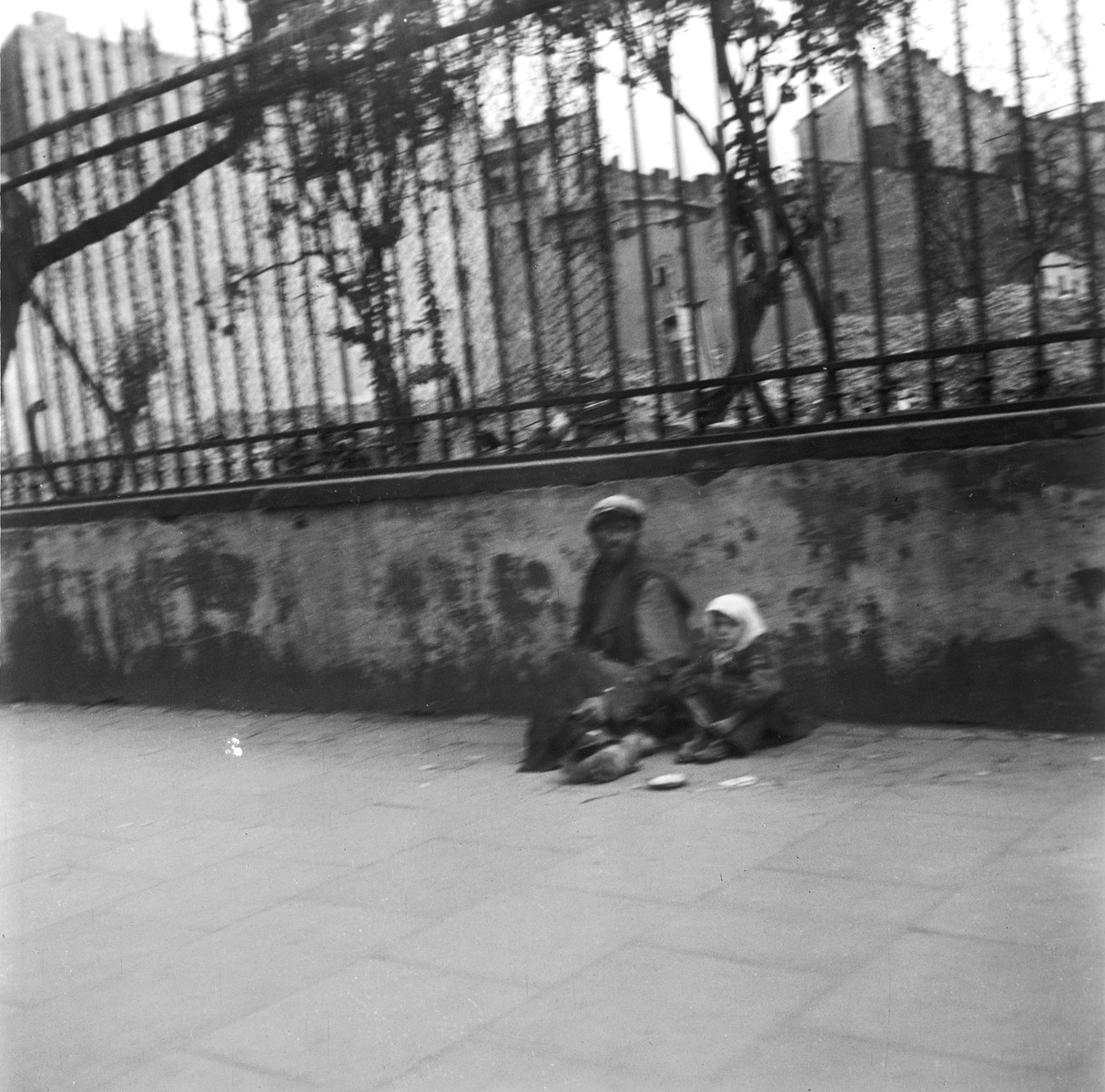 "A destitute man and child sit against a wall on a street in the Warsaw ghetto.  Joest's original caption reads: ""A man and child, both without shoes, gazed at me in silence.  In front of them a beggar's bowl."""