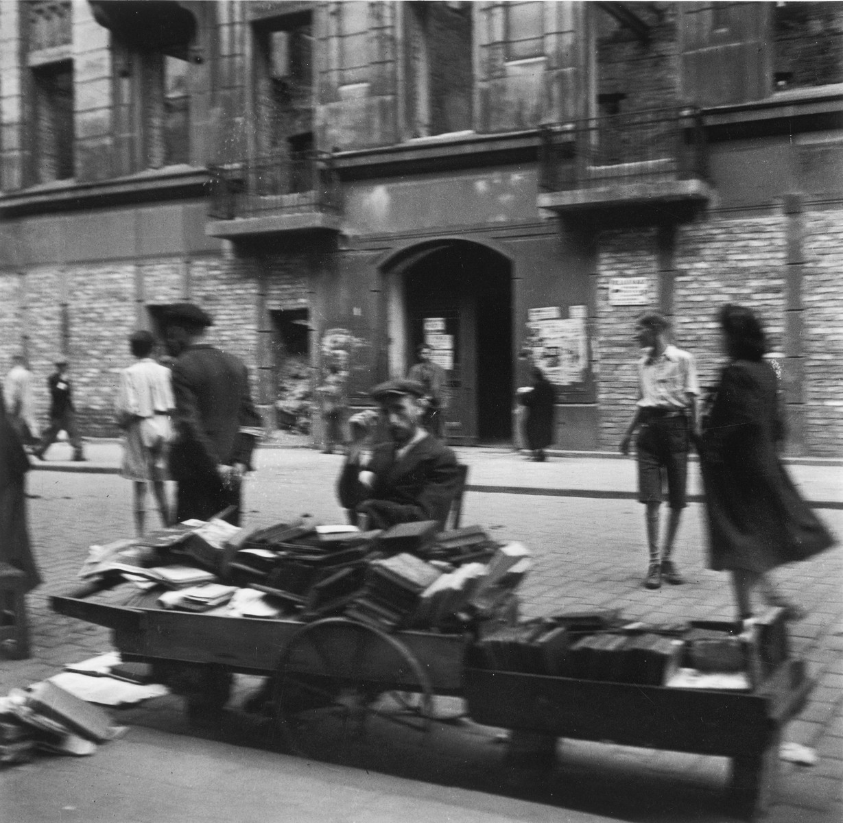 """A vendor sells used books on a street in the Warsaw ghetto.  Joest's original caption reads: """"I remember quite clearly that I asked myself how these people could buy books when they had nothing to eat.  I don't recall the location of this picture.  There were many such book carts."""""""