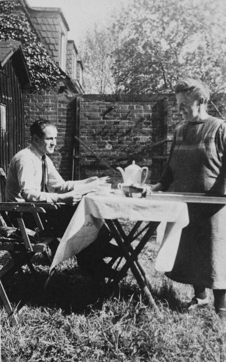 A German-Jewish couple enjoys a cup of coffee in their garden.  Pictured are members of the Bähr family.  Taken from the photo album of Margot Bähr.