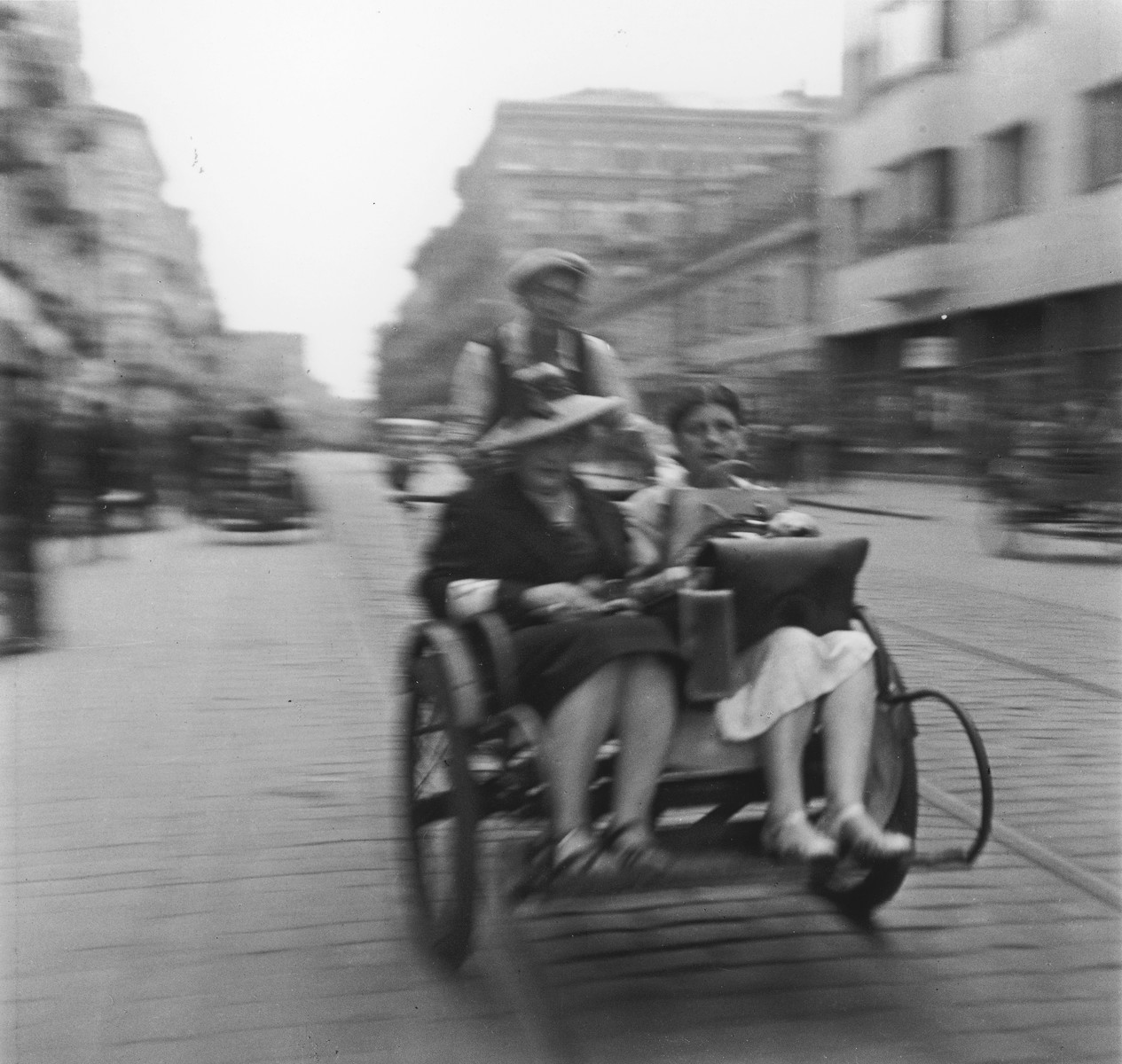 """Two Jewish women ride in a rickshaw along a street in the Warsaw ghetto.  Joest's original caption reads: """"Apparently two well-to-do women taking a ride home after shopping."""""""