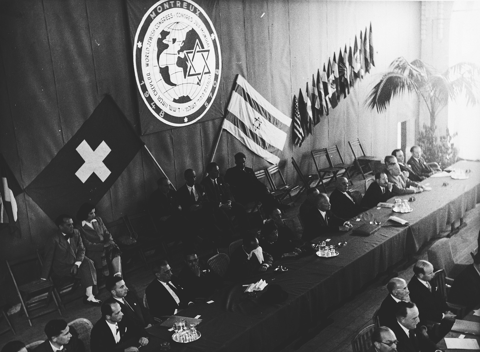 The Presidium at the opening session of the Assembly of the World Jewish Congress in Montreux, Switzerland. Among those pictured is Gerhart Riegner (second row, third from the left, bended forward).