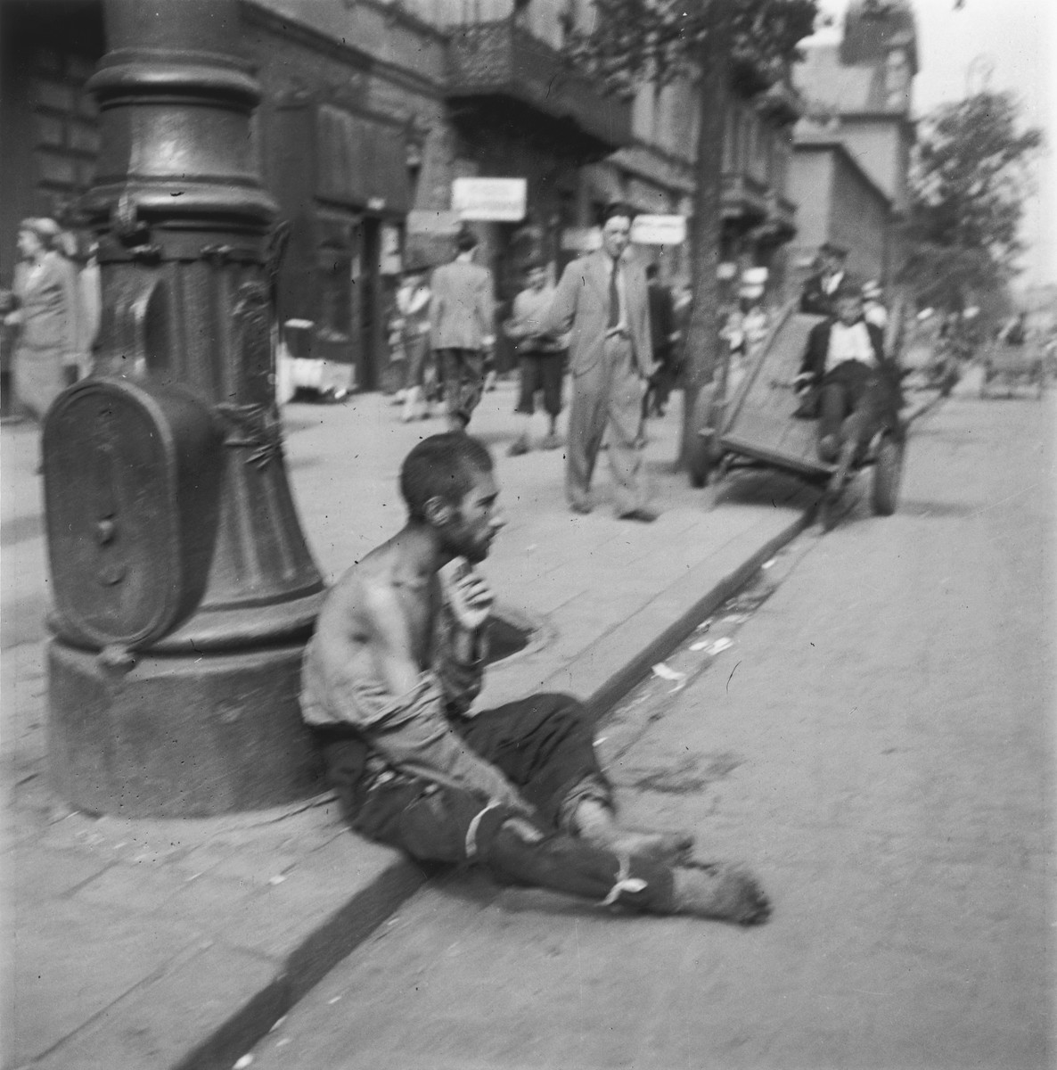 "A destitute man sits on a curb in the Warsaw ghetto.  Joest's original caption reads: ""Everthing this man was wearing was kaputt.  His right leg was bound up with two strips of cloth as if they were injured."""