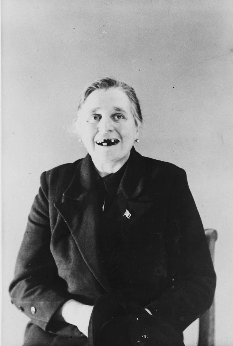 A female survivor shows her missing teeth as a result of her incarceration in the Breendonck internment camp.