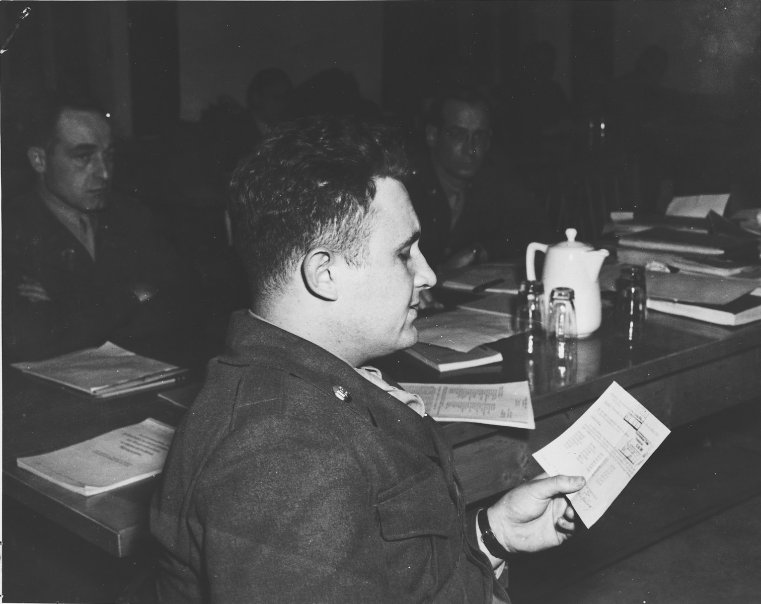 An American military lawyer examines a document during the Dachau war crimes trial.