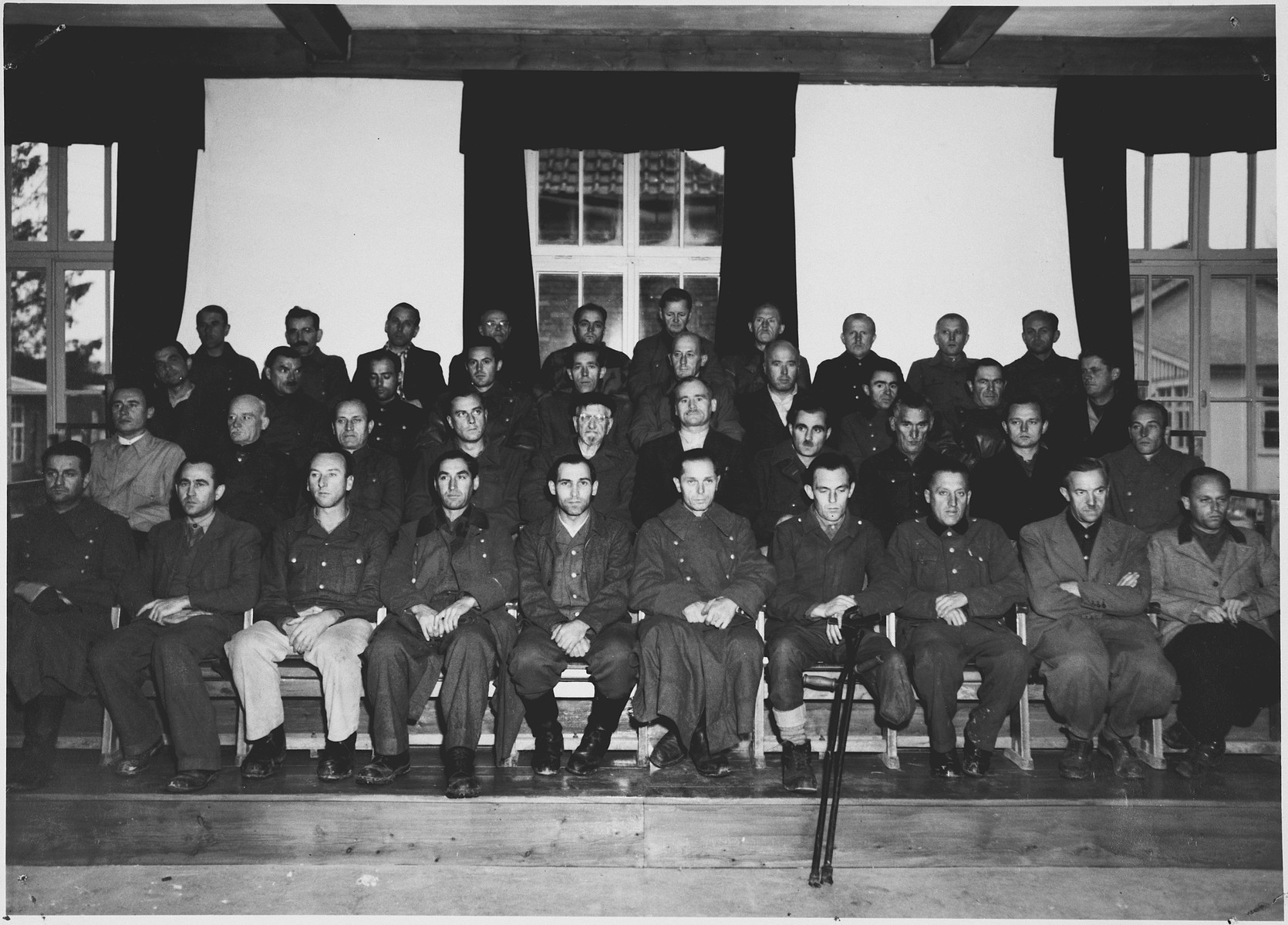 Group portrait of the defendants in the Dachau war crimes trial.  Among those pictured (front row, fifth from the right) is Josef Seuss, SS-Hauptscharfuehrer and a guard or warden at Dachau from 1933 to 1942.  He was convicted of war crimes, and executed at the Landsberg am Lech prison in  May 1946.