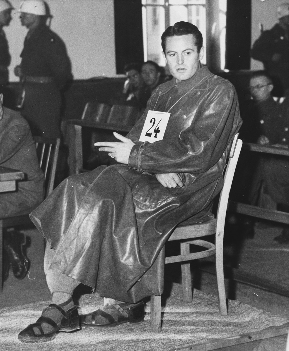 Defendant Rudolf Heinrich Suttrop takes the stand in the Dachau trial.    Rudolf Heinrich Suttrop (b. 7/17/11) was an SS Obersturmfuehrer.  He served as an adjutant in the Dachau concentration camp from 1942-1944.  He was convicted and hanged on May 28, 1946.