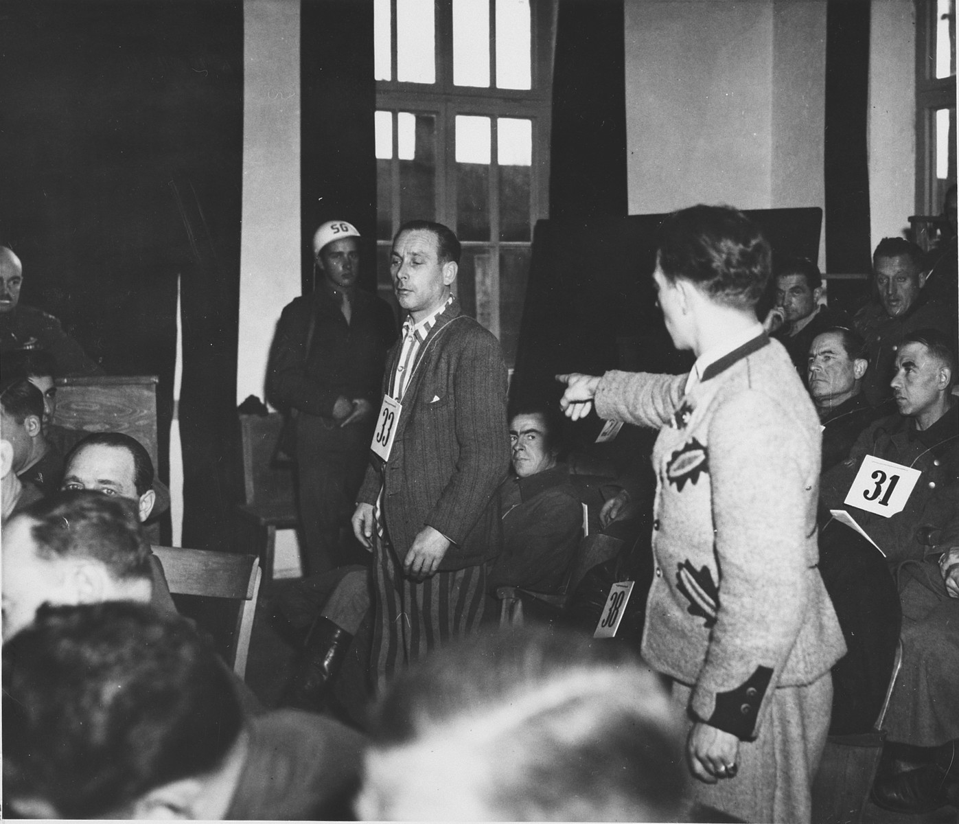 A prosecution witness points out defendant Emil Erwin Mahl during the Dachau war crimes trial.