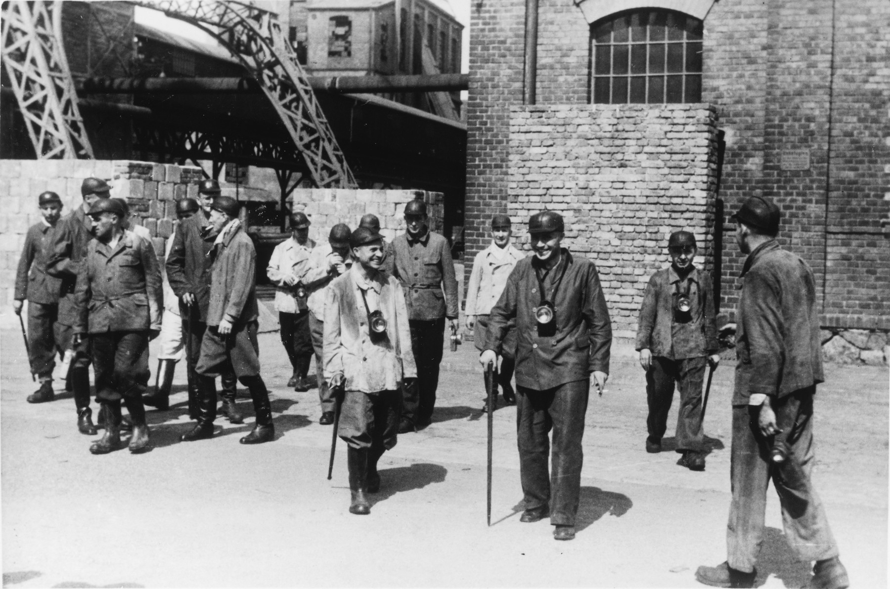 "A large group of SS officers visit a coal mine near Auschwitz.  The original caption reads ""Besichtigung eines Kohlenbergwerks."" (visiting a coal mine)  Karl Hoecker is in the center with a cane.  Behind Hoecker is Dr. Fritz Klein.  Pictured on the left are Heinz Baumkoetter, Eduard Wirths and Alfred Trzebinski.  Walking on the left with a cigarette is Dr. Enno Lolling."