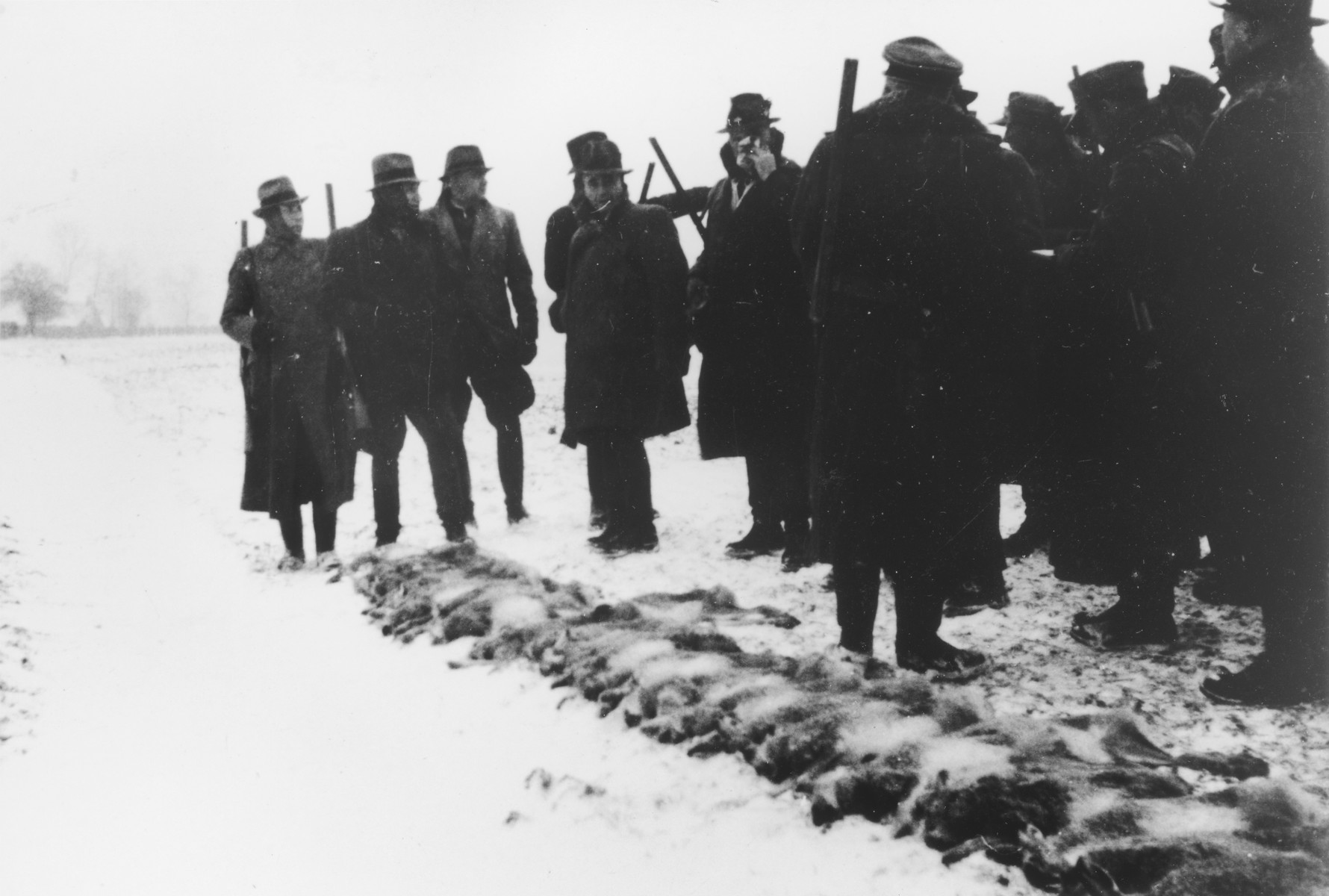 """Several SS officers stand with their shotguns during a winter hunting excursion.    The original caption reads """"Treibjagd bei Schnee"""" (going hunting in the snow).   Karl Hoecker is on the far left and Karl Moeckel is third from the left."""