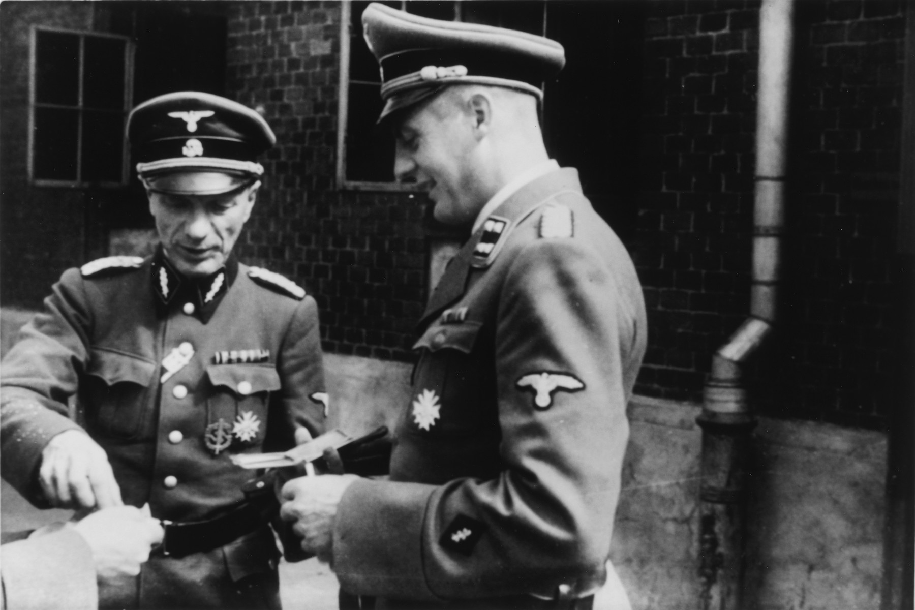 Two SS officers meet during the dedication of the new SS hospital in Auschwitz.  Pictured on the far left is Dr. Enno Lolling and on the right is Dr. Eduard Wirths.  Dr. Wirths also received his promotion to Sturmbannfuehrer and decorated with the War Service Cross 1st Class at the same time and this might be what is being portrayed here.