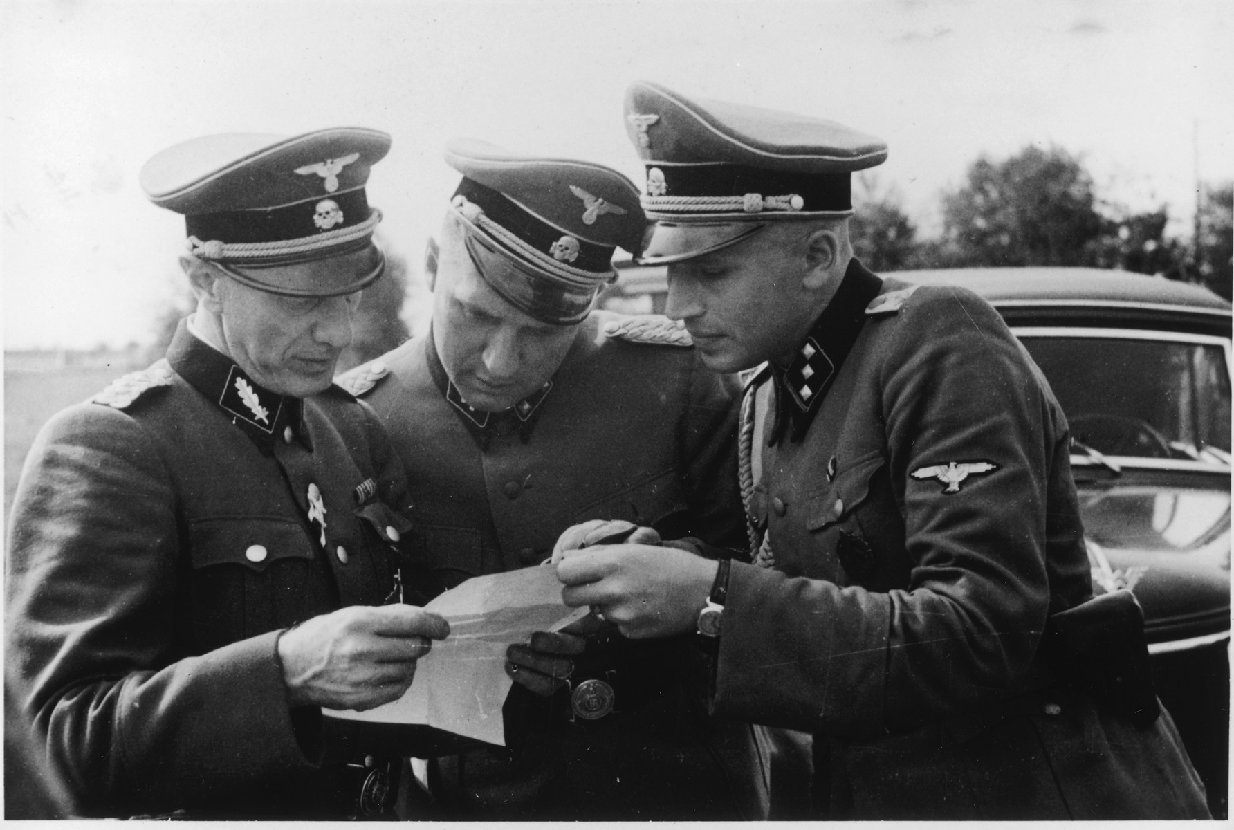 Three SS officers study a document during the dedication of the new SS hospital.  Pictured left to right are Dr. Enno Lolling, Commandant Richard Baer and Adjutant Karl Hoecker.