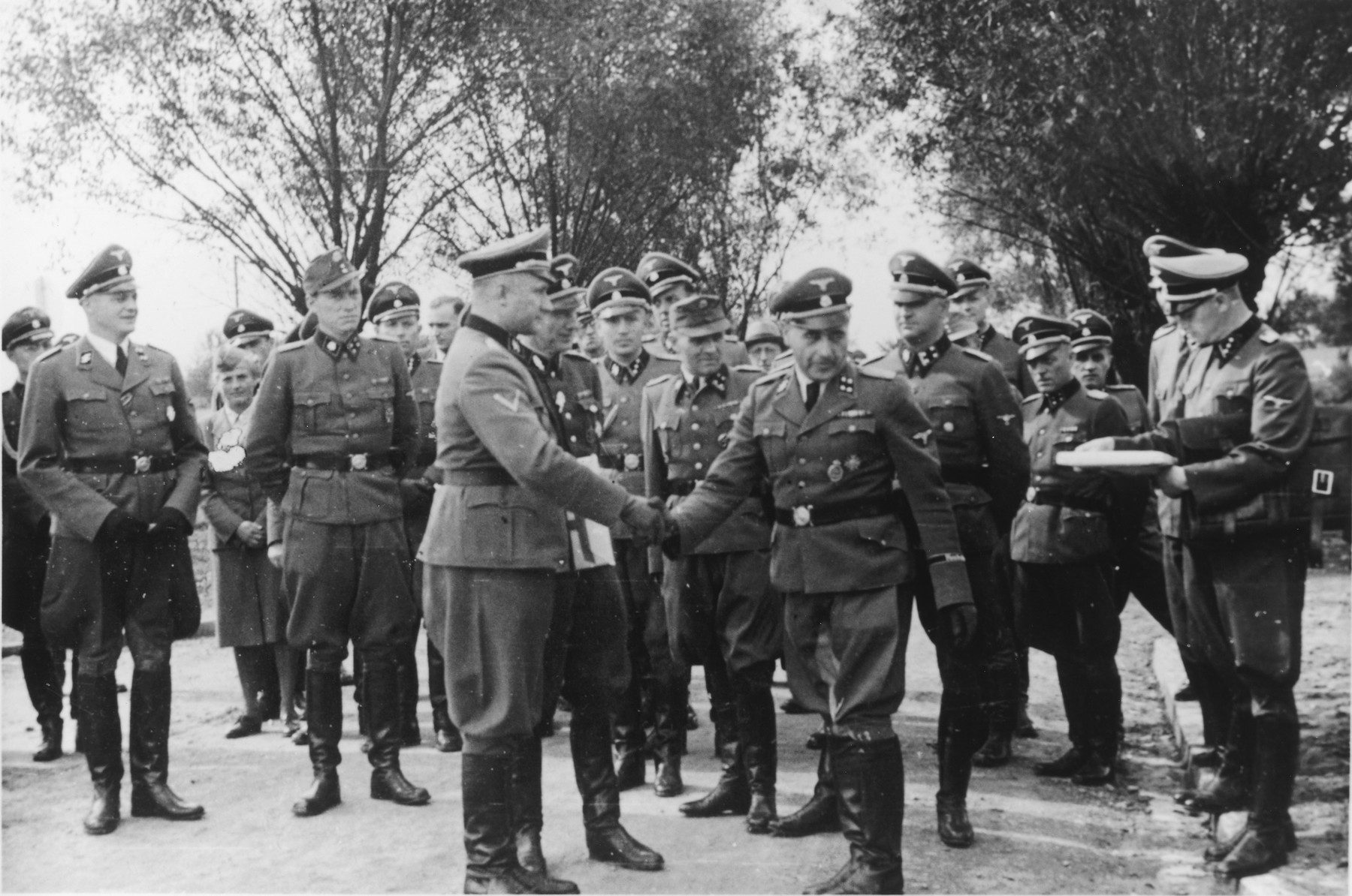 "Nazi officers watch Commandant Richard Baer  shakes hands with Karl Bischoff during the dedication of the new SS hospital in Auschwitz.  The original caption reads ""Besichtigung"" (tour).  Also pictured are Dr. Eduard Wirths standing on the far left, Dr. Heinz Baumkoetter (sixth from left), Karl Hoecker and Rudolf Hoess.  Holding the documents on the right is (most probably Werner Jothann).  To the right of Wirths, is (probably August Harbaum, adjutant to Richard Gluecks).   Between Wirths and Harbaum is probably Maria Mandl.  Also pictured are Enno Lolling and Karl Moeckel."