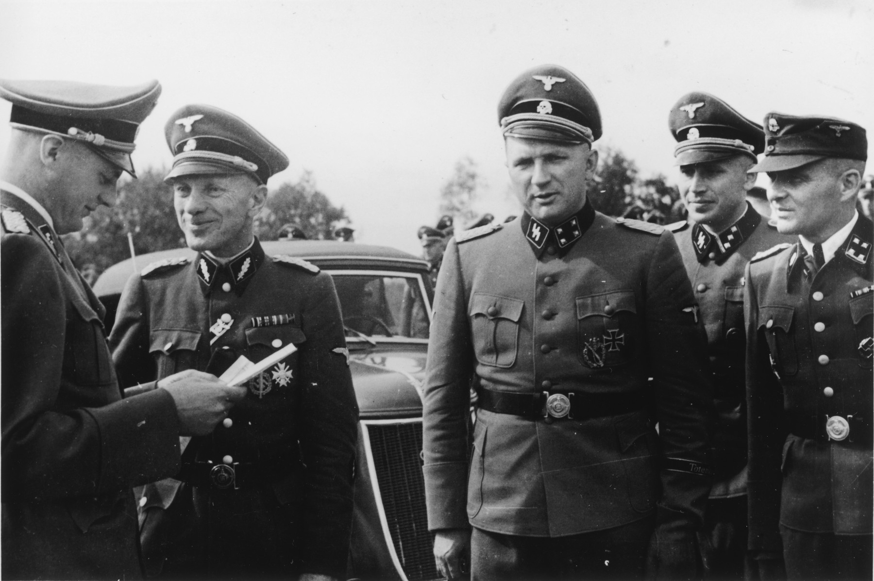 A group of SS officers gathers during the dedication of the new SS hospital.  Pictured left to right are Dr. Eduard Wirths, Dr. Enno Lolling, Commandant Richard Baer, Adjutant Karl Hoecker and former Commandant Rudolf Hoess.   Dr. Wirths also received his promotion to Sturmbannfuehrer and decorated with the War Service Cross 1st Class at the same time and this might be what is being portrayed here.