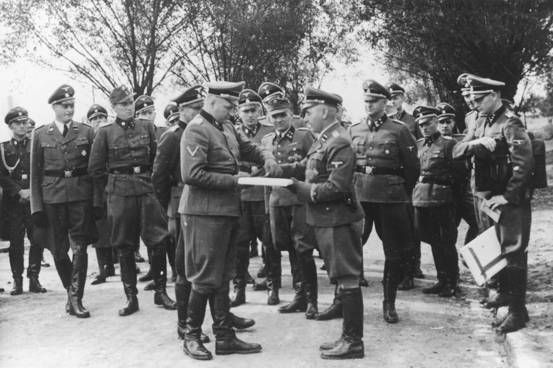 "Nazi officers watch as Commandant Richard Baer exchanges documents with Karl Bischoff during the dedication of the new SS hospital in Auschwitz.  The original caption reads ""Besichtigung"" (tour).  Dr. Eduard Wirths stands on the far left.  Dr. Heinz Baumkoetter is fifth from the left.  In the center are Commandant Richard Baer, Karl Hoecker and Rudolf Hoess and Karl Moeckel.  Holding the documents on the right is (most probably Werner Jothann). To the right of Wirths, is (probably August Harbaum, adjutant to Richard Gluecks)."