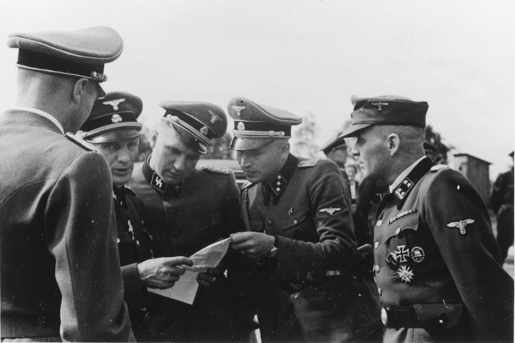 Several SS officers study a document during the dedication of the new SS hospital.  Pictured facing the camera left to right are Dr. Enno Lolling, Commandant Richard Baer and Adjutant Karl Hoecker and former Commandant Rudolf Hoess.  Standing with his back to the camera is probably Dr. Eduard Wirths.