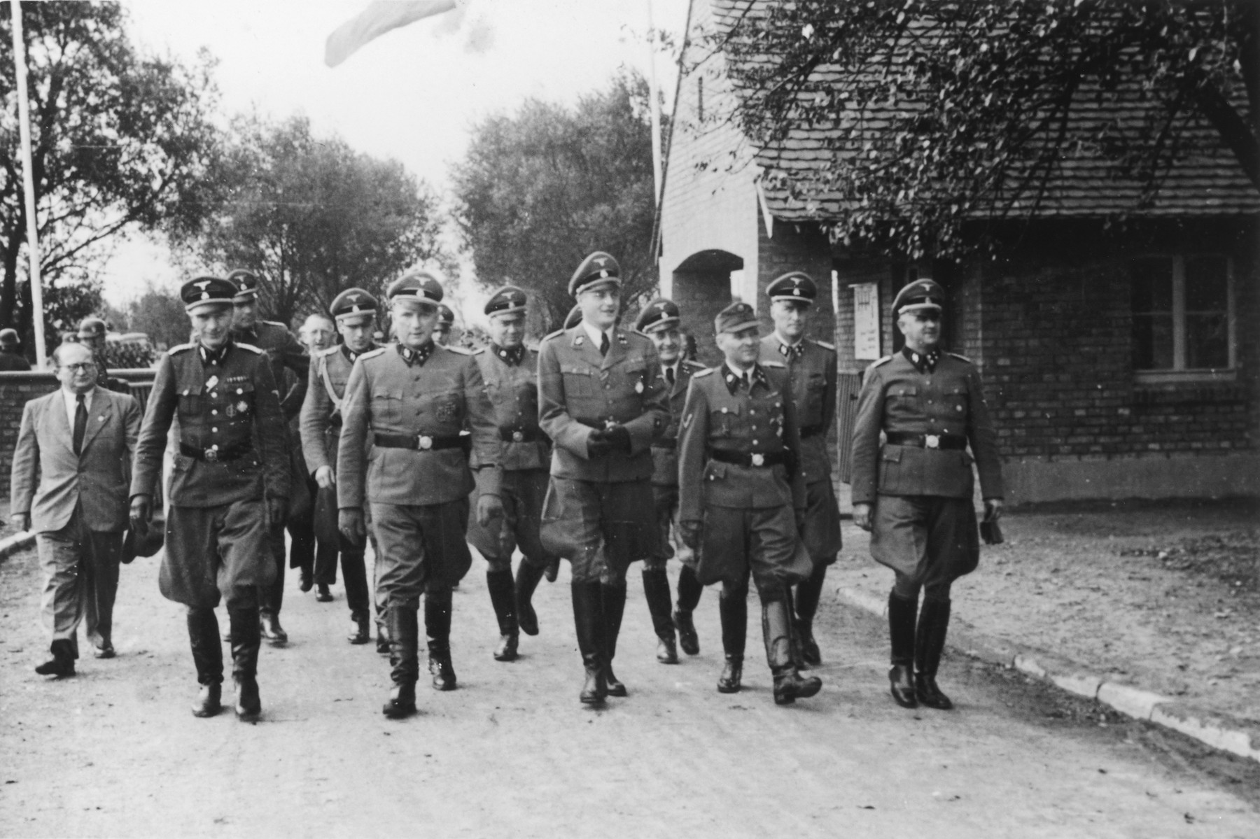 """Nazi officers walk towards the dedication of the new SS hospital in Auschwitz.  The original caption reads """"Besichtigung"""" (tour).  Standing in front are Dr. Carl Clauberg, Dr. Enno Lolling,  Commandant Richard Baer, Dr. Eduard Wirths, Rudolf Hoess and Karl Moeckel.  Also pictured in the second row are Josef Kramer, Karl Hoecker, and Karl Bischoff. Pictured in the very back is Johannes Paul Goebel."""