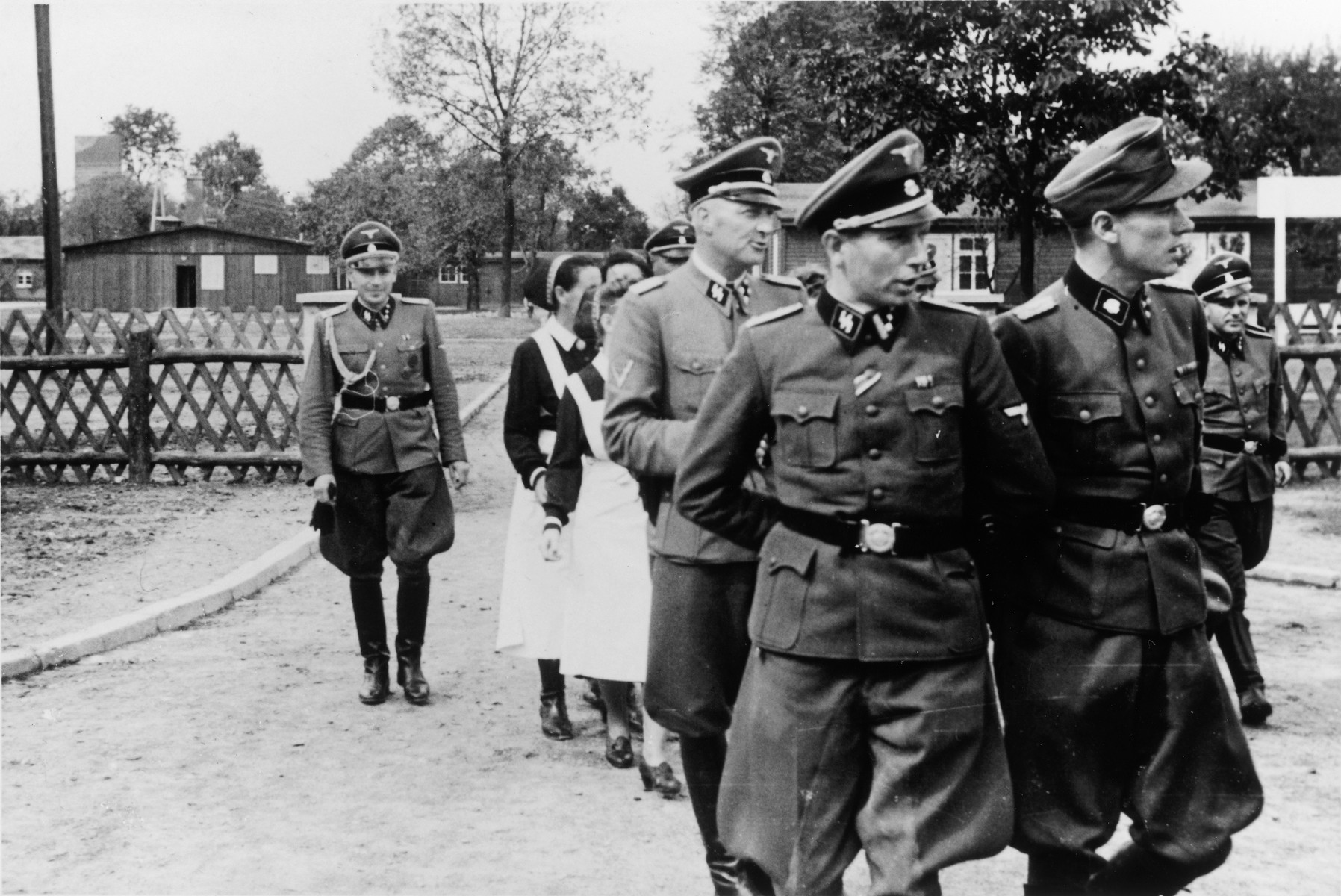 SS officers and German nurses attend the dedication ceremony of the new SS hospital in Auschwitz.  Among those pictured is Heinz Baumkoetter (front left) and Karl Hoecker (back, left).