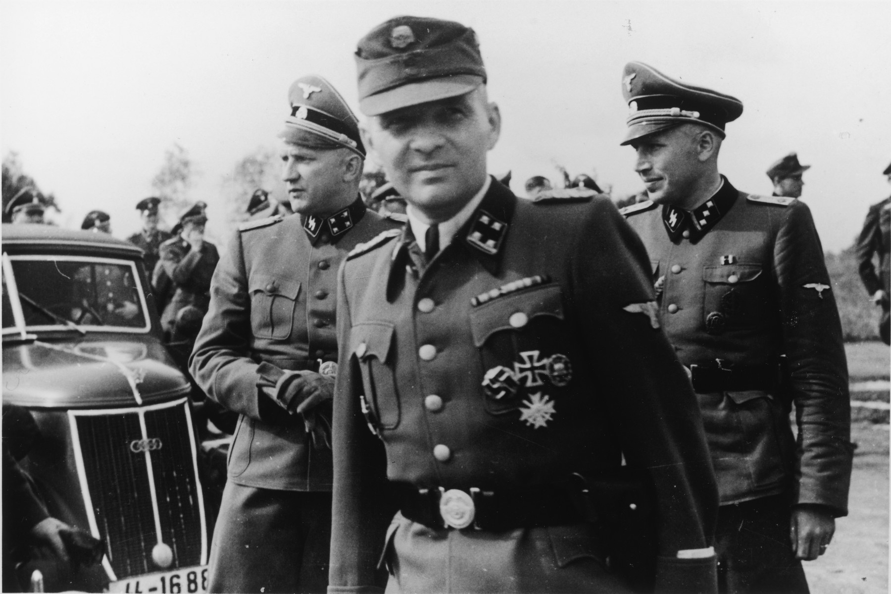 Three SS officers stand next to an automobile during the dedication ceremonies of the new SS hospital.  Pictured left to right are Richard Baer, Rudolf Hoess and Karl Hoecker.