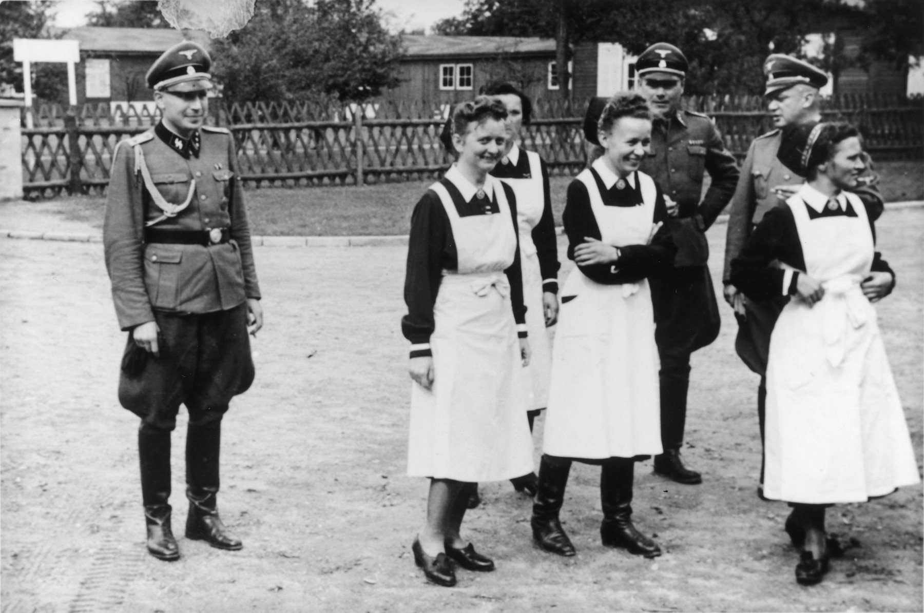 SS officers and German nurses gather during the dedication ceremony of the new SS hospital in Auschwitz.  Among those pictured are Karl Hoecker, Josef Kramer and SS-Hauptsturmfuhrer Heinrich Schwarz.  Among the nurses probably are Martha Mzyk and Lotte Nitschke.