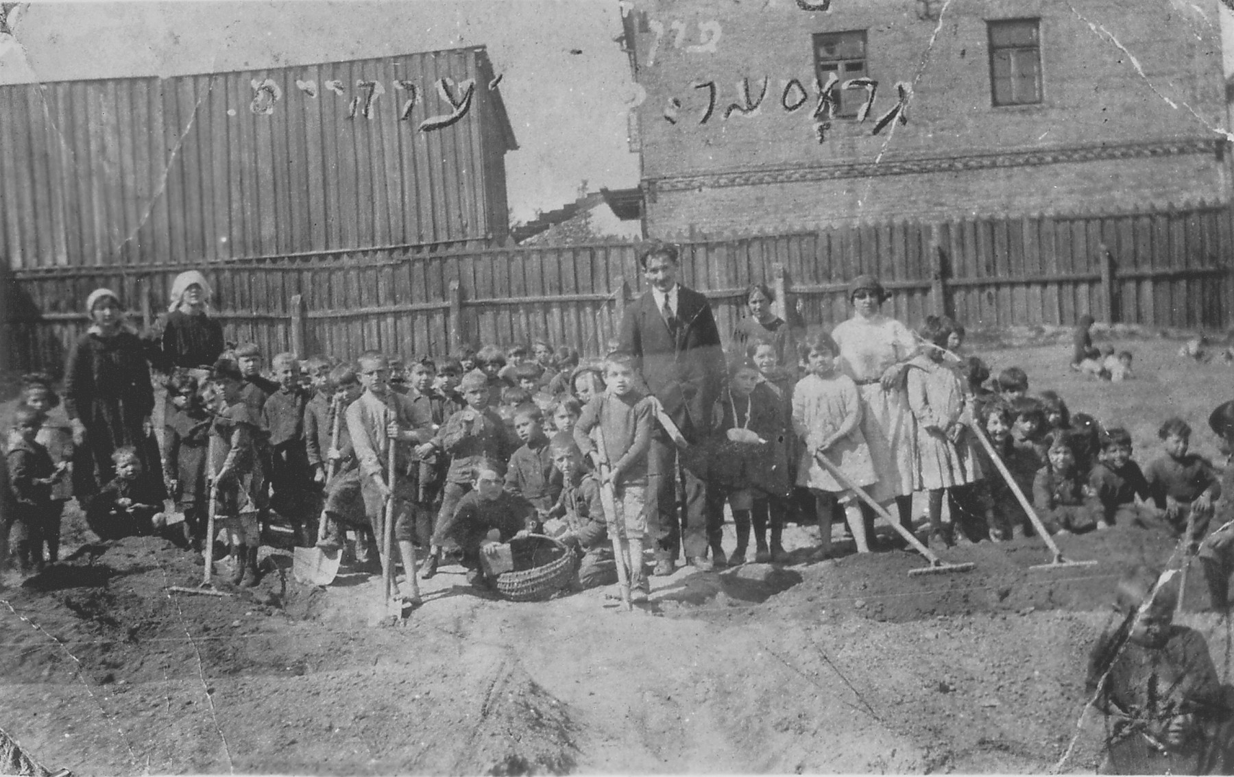 Students from the Bialystok Yiddish school raking in a yard.  Icchok Melamedowicz taught mathematics at this school.