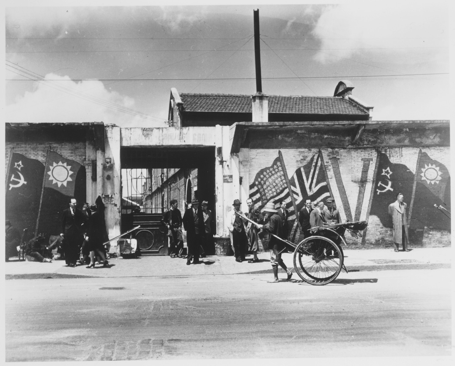 A rickshaw driver passes Heime decorated with a victory painting of Allied flags.